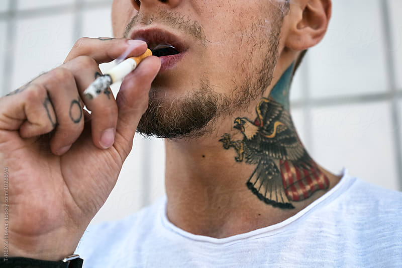 Close-up of tattooed man smoking cigarette by Danil Nevsky for Stocksy United