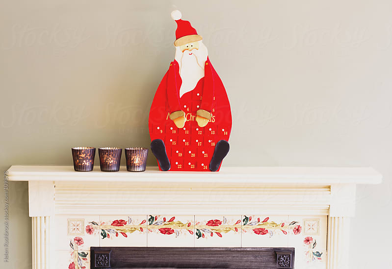 Tea lights and an advent calendar on a mantlepiece by Helen Rushbrook for Stocksy United