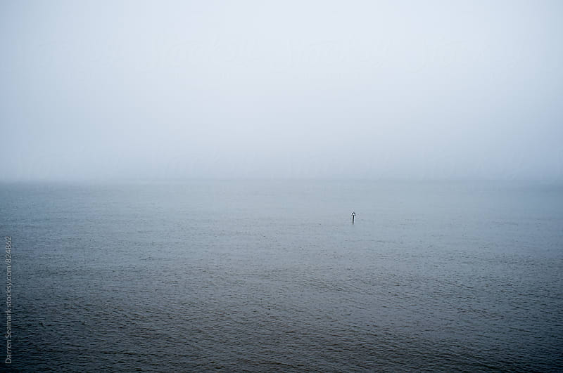 An object floating in a fog engulfed sea by Darren Seamark for Stocksy United