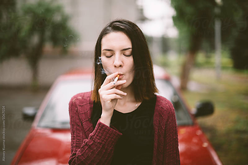 portrait of real young smoking woman by Alexey Kuzma for Stocksy United