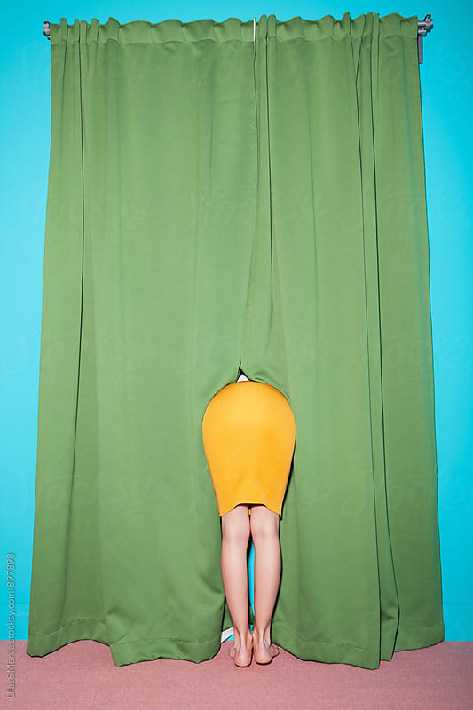 woman hiding behind the green curtain by Ulaş and Merve for Stocksy United