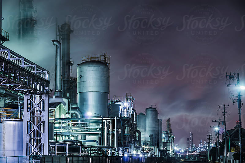 Busy chemical factories at night next to a residential area by yuko hirao for Stocksy United