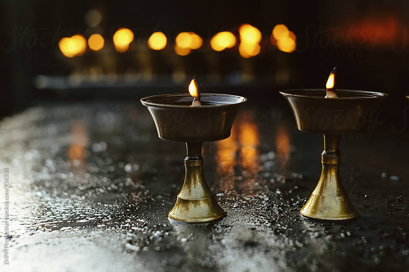 Oil lamps in the temple by Artem Zhushman for Stocksy United
