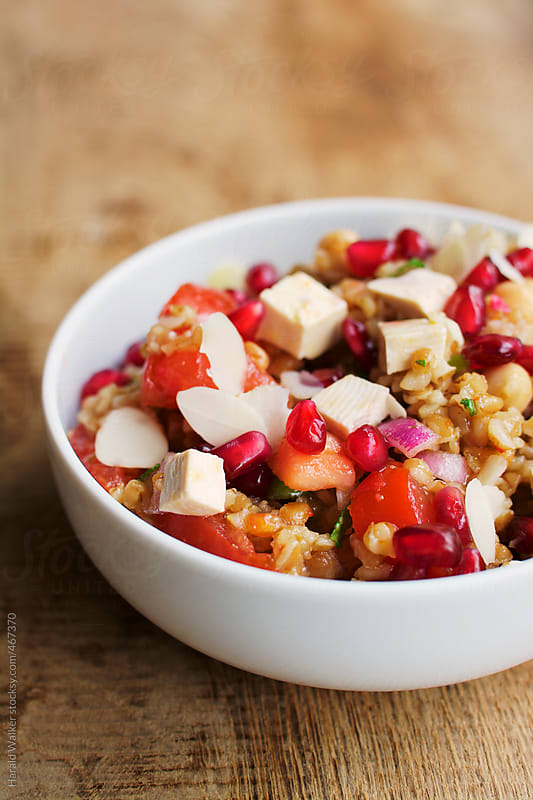 Bulgur Tomato Salad with Pomegranate Arils Mint and Almonds by Harald Walker for Stocksy United