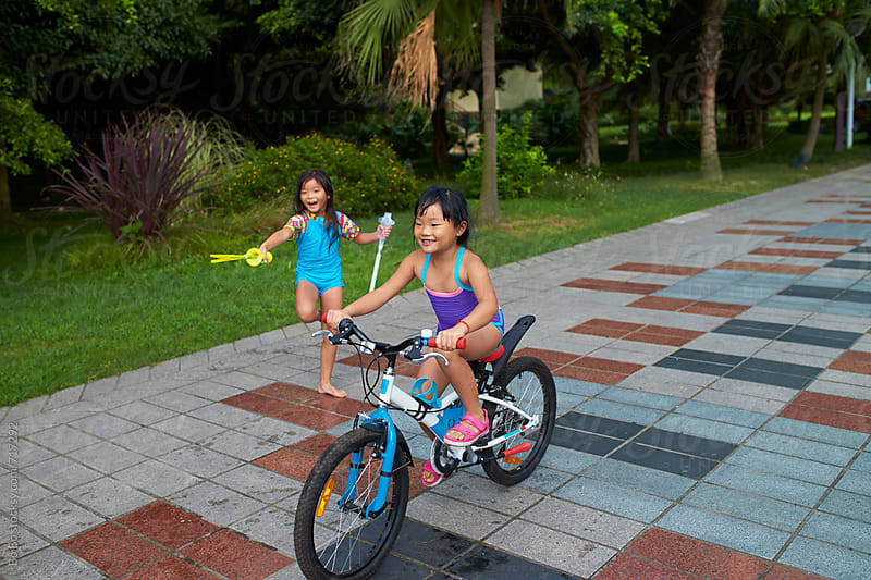 happy kids riding bike in the park by Bo Bo for Stocksy United