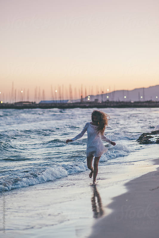 woman enjoying the sunset on the beach by Javier Pardina for Stocksy United