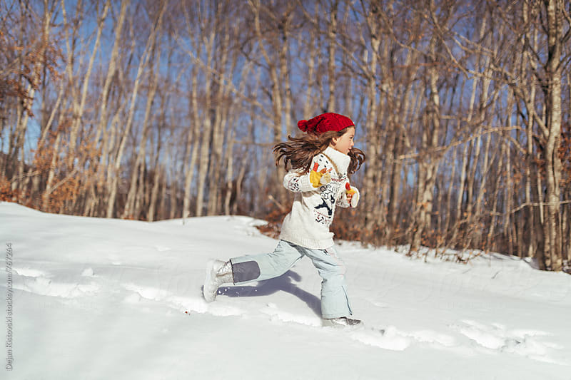 Child playing on the snow by Dejan Ristovski for Stocksy United