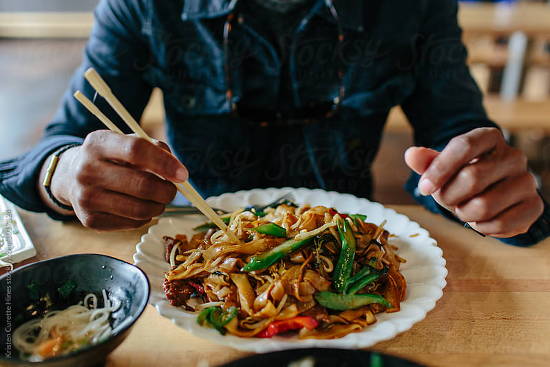 Close up of a man eating stir fry  by Kristen Curette Hines for Stocksy United