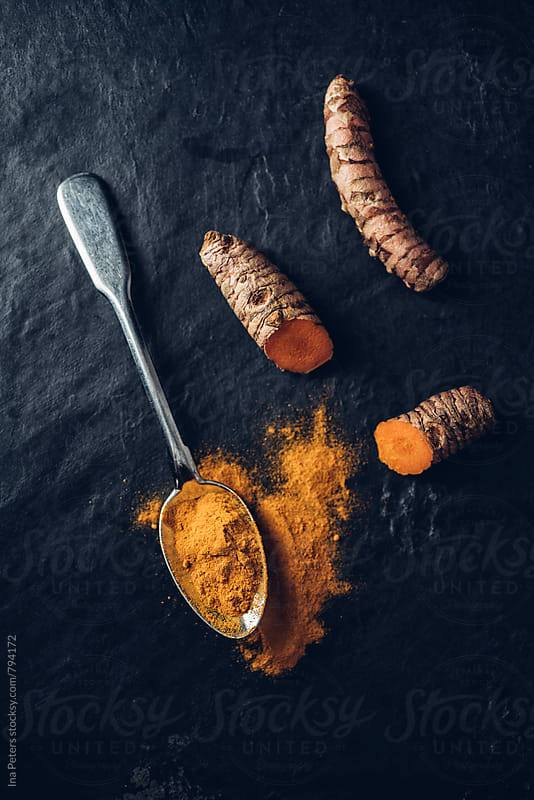 Food: Curcuma root and powder on spoon by Ina Peters for Stocksy United