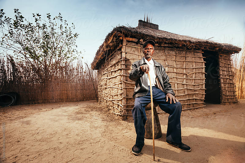 Proud African Hambukushu man outside his mud hut by Micky Wiswedel for Stocksy United