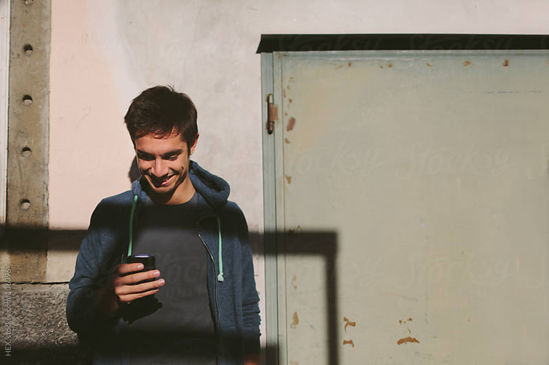 Man Reading Message on the Mobile Phone  by HEX. for Stocksy United