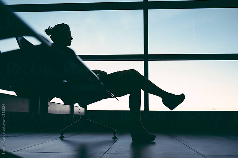 Businesswoman sitting in airport lounge by GIC for Stocksy United