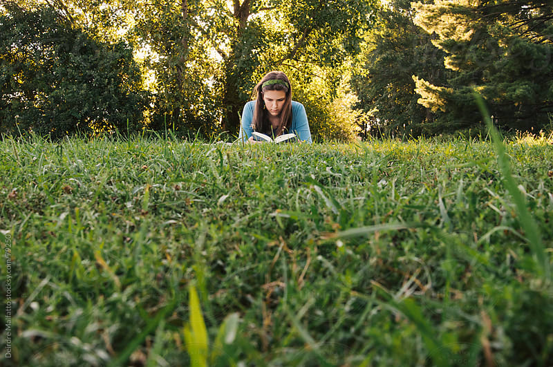 Teen girl reading book outside in field by Deirdre Malfatto for Stocksy United