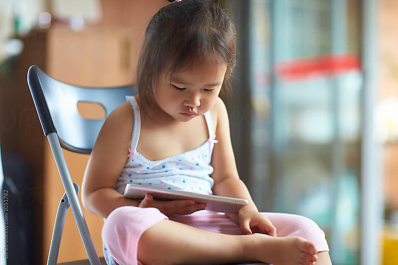Little girl using tablet indoor by cuiyan Liu for Stocksy United