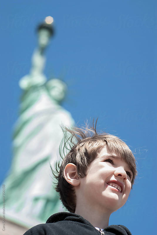 Boy stands at the base of the Statue of Liberty, looking over New York Harbor Harbor by Cara Dolan for Stocksy United