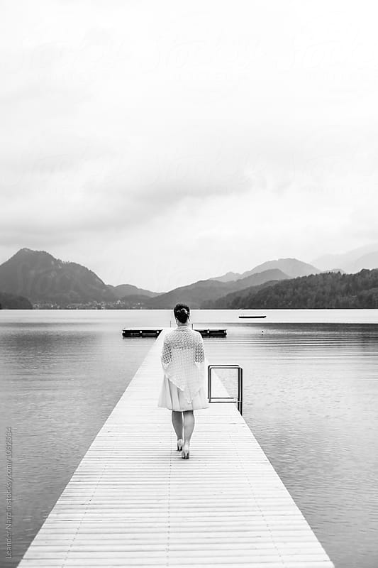 bride walking along a jetty in beautiful lake landscape - black and white by Leander Nardin for Stocksy United