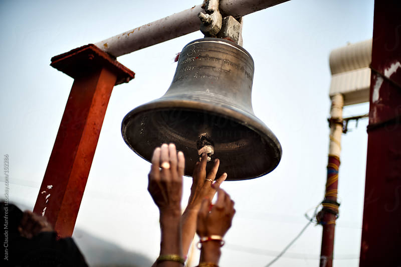 Women ring the Sacred Bell before starting the ritual bath in the Ganges by Jean-Claude Manfredi for Stocksy United