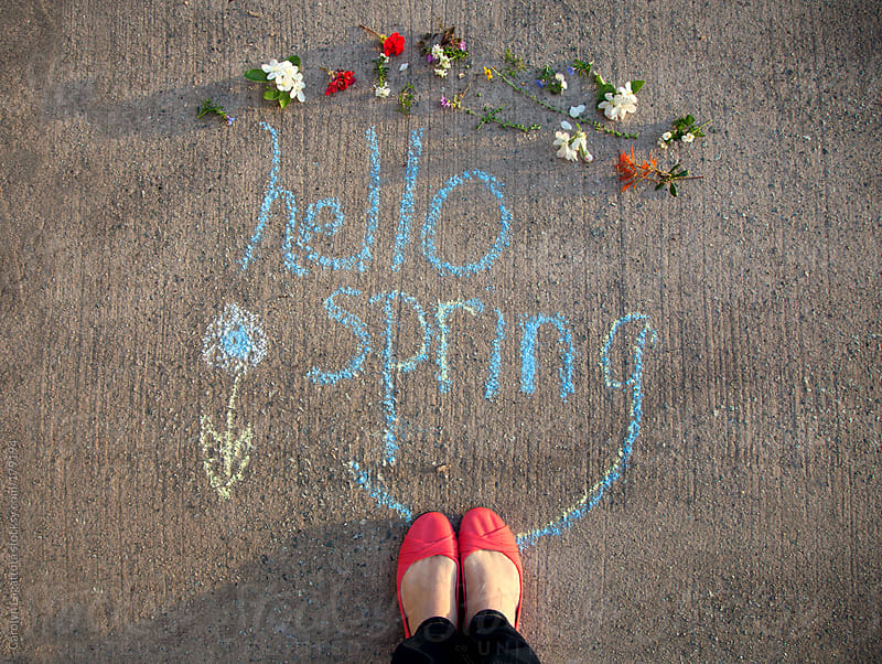 Chalk message, flowers and orange shoes welcoming the first day of Spring by Carolyn Lagattuta for Stocksy United