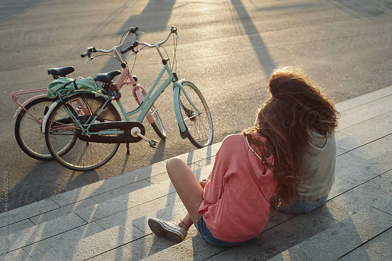 Two young girls with bikes enjoying the last sun rays in Barcelona city by Miquel Llonch for Stocksy United
