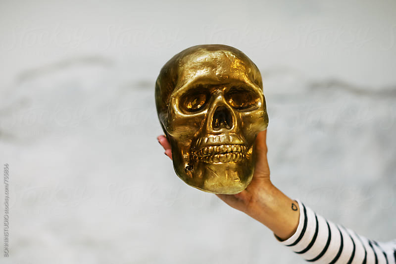 Hand holding a gold skull.  by BONNINSTUDIO for Stocksy United