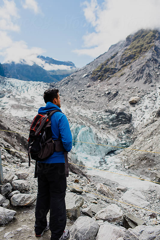 Young man from behind contemplating a glacier coming down from the mountain by Leandro Crespi for Stocksy United