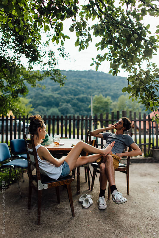 Friends enjoying a beer and cigarette in the garden by Boris Jovanovic for Stocksy United