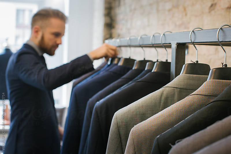 Men's Fashion Shopping - High-End Suits Hanging on Clothing Rack by Julien L. Balmer for Stocksy United