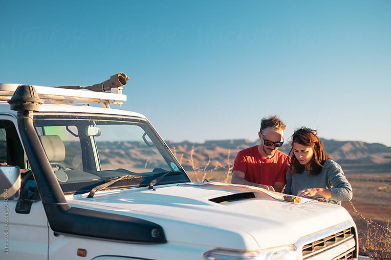 Couple reading a map on the hood of their car in the wilderness by Micky Wiswedel for Stocksy United