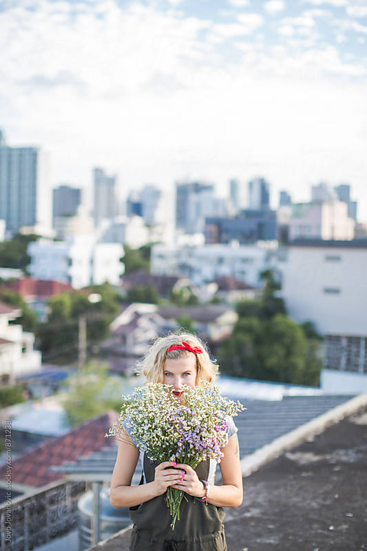 Beautiful woman standing on a rooftop and holding bouquet of wildflowers by Jovo Jovanovic for Stocksy United