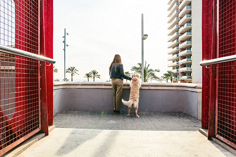 Back view of a woman and her dog on a bridge. by BONNINSTUDIO for Stocksy United