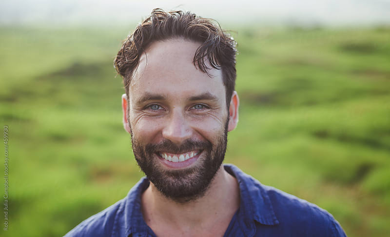 Bearded man with brown hair looking happy outside in nature by Rob and Julia Campbell for Stocksy United