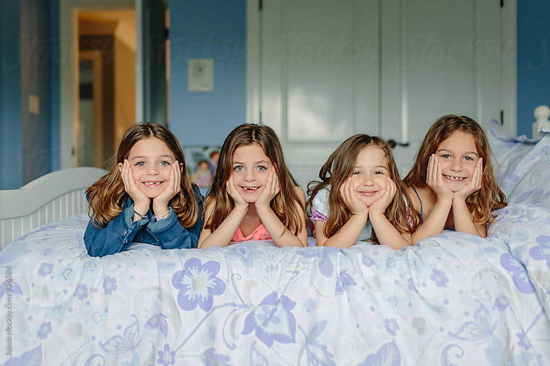 Four cute young girls laying together on a bed by Jakob for Stocksy United