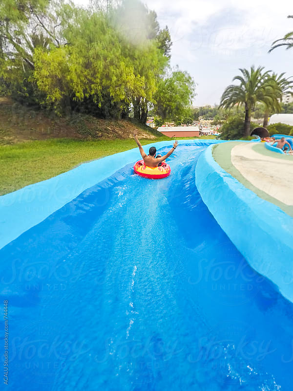 Man with an inflatable mattress on a waterpark by ACALU Studio for Stocksy United