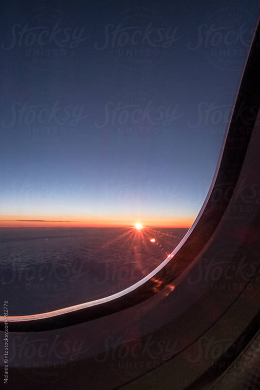 Sunrise seen from an airplane by Melanie Kintz for Stocksy United