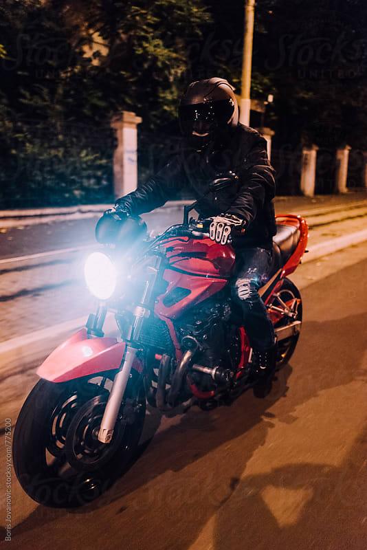 Man riding a bike on empty streets by night by Boris Jovanovic for Stocksy United