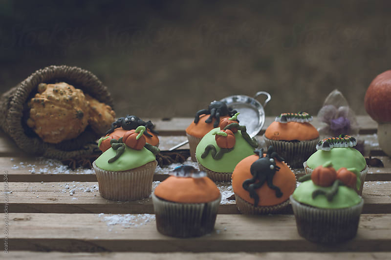 Halloween theme cupcakes with sprinkled powdered sguar on table by Beatrix Boros for Stocksy United