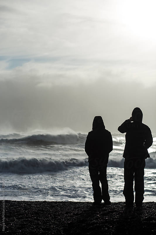 Silhouettes watching the Iceland waves by Reece McMillan for Stocksy United