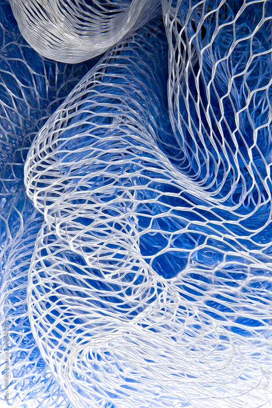 Closeup macrophotograph of the interweaving of a plastic mesh fabric by Ron Mellott for Stocksy United