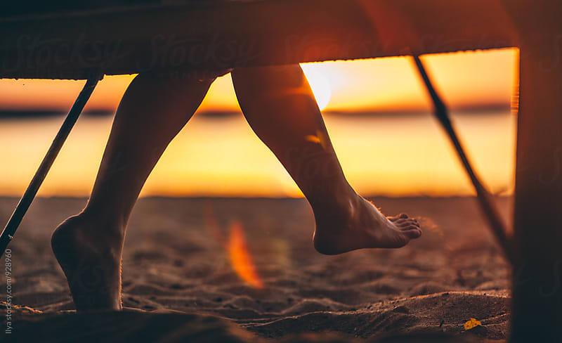 Woman sitting on beach bench swinging legs by Ilya for Stocksy United