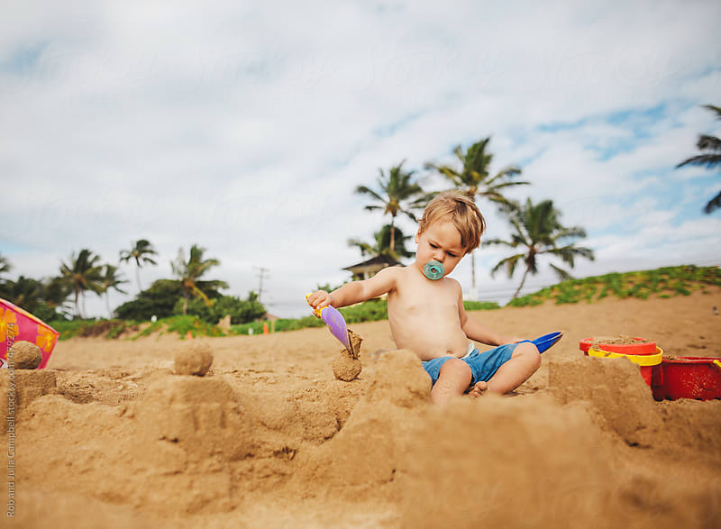 Toddler boy working on sandcastle on sandy tropical beach alone by Rob and Julia Campbell for Stocksy United