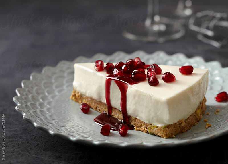 Cheesecake with Pomegranate seeds and syrup dripping on frilly dish by Sherry Heck for Stocksy United