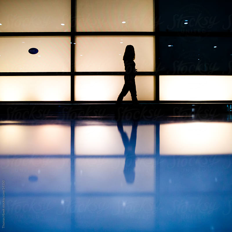 Woman walking in airport in silhouette with reflection by Thomas Hawk for Stocksy United