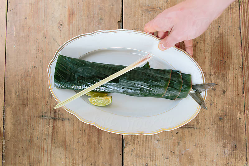 Fish rolled in banana leaf  with lemongrass by Denni Van Huis for Stocksy United