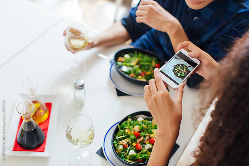 Woman taking a photo of her salad from above.  by BONNINSTUDIO for Stocksy United