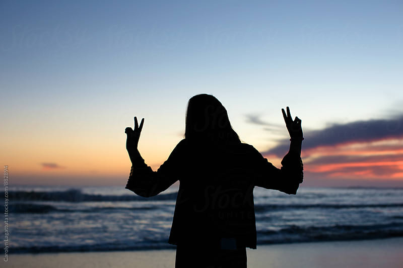Teenage girl flashing peace signs at sunset by Carolyn Lagattuta for Stocksy United