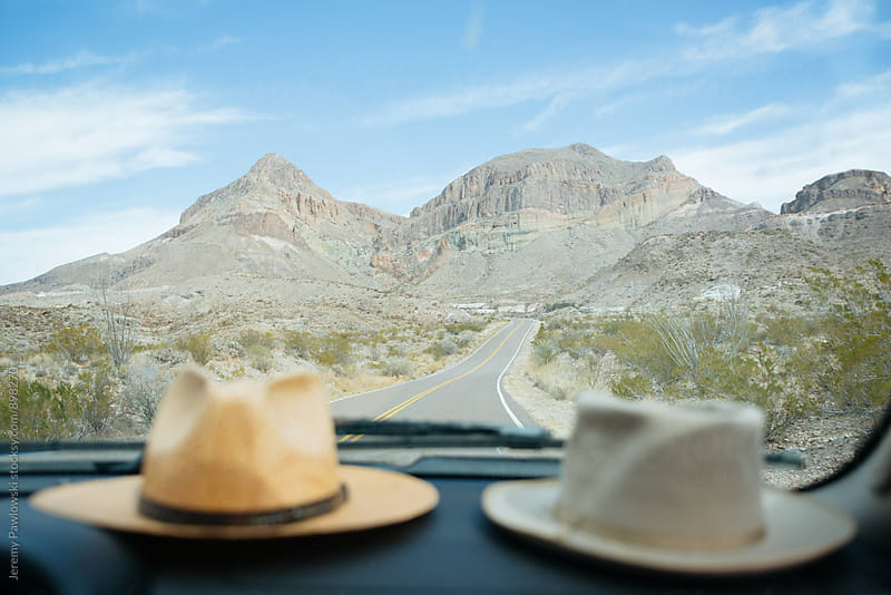 Hats on dashboard with road and mountain in background by Jeremy Pawlowski for Stocksy United