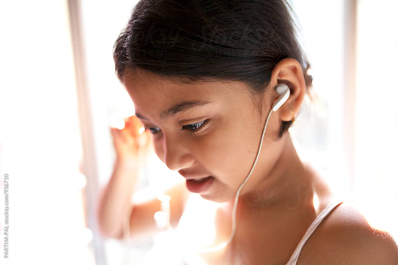 A girl enjoy conversation with mobile headset by PARTHA PAL for Stocksy United