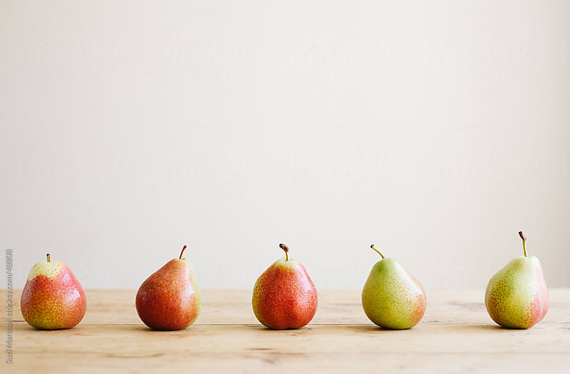 Five Forelle pears in a line on a wooden table by Suzi Marshall for Stocksy United