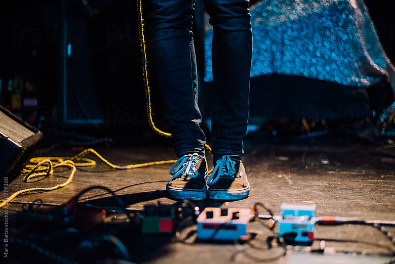 Feet on the stage near to the guitar pedals by María Barba for Stocksy United