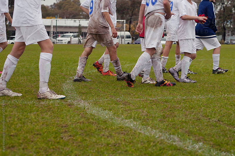 Muddy football team walking off field by skye torossian for Stocksy United